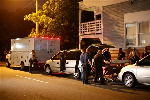 A body is moved from a crime scene at an apartment complex where five members of a family, including three children, were found dead authorities said Sunday, July 27, 2014, in Saco, Maine.