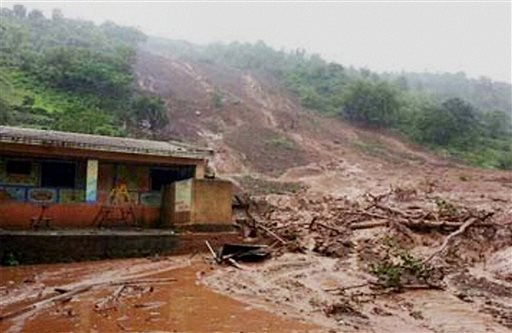 Mud and slush surround a building after a mudslide in Malin village, in the western Indian state of Maharashtra, Wednesday, July 30, 2014. (AP Photo/Press Trust of India)