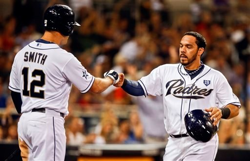 San Diego Padres' Rene Rivera is congratulated by Seth Smith, left, after scoring from third on a sacrifice fly by Alexi Amarista against the St. Louis Cardinals in the third inning of a baseball game Tuesday, July 29, 2014, in San Diego.