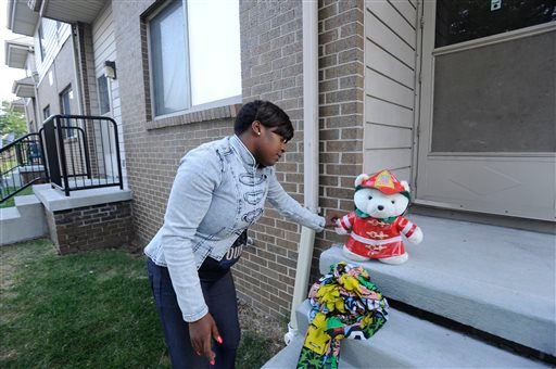 Beatrice Spears leaves a stuffed animal on the front porch of a home where an 8-year-old boy was shot and killed by a bullet fired from outside that pierced the wall of his home, hitting the child in bed, early Wednesday, July 30, 2014. (AP Photo)