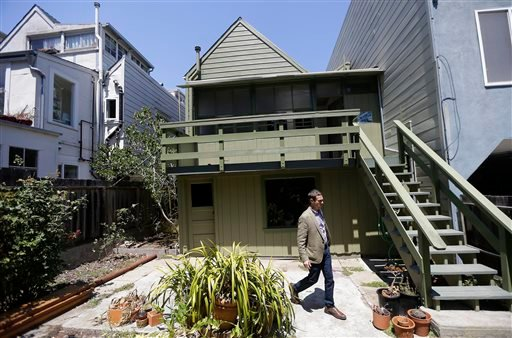 George Limperis, a realtor with Paragon Real Estate Group, walks in the backyard of a property in the Noe Valley neighborhood in San Francisco.
