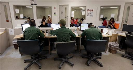 This June 18, 2014 file photo shows U.S. Customs and Border Protection agents working at a processing facility in Brownsville,Texas.