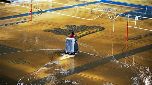 A worker begins the task of cleaning up at least an inch of water covering the playing floor at Pauley Pavilion. (AP)