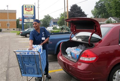 Sharon Green loads bottled water into her car she bought after Toledo warned residents not to use its water, Saturday, Aug. 2, 2014 in Toledo, Ohio.