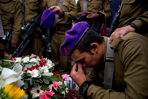 Israeli soldiers mourn over the grave of Israeli Army 2nd. Lt. Hadar Goldin during his funeral at the military cemetery in the central Israeli city of Kfar Saba on Sunday, Aug. 3, 2014.
