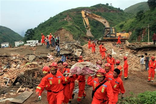 Rescue workers remove a dead body from the remains of a collapsed building at the epicenter of an earthquake that struck the town of Longtoushan in Ludian county in southwest China's Yunnan province Monday, Aug. 4, 2014.