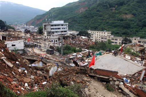 Rescue workers search for survivors among the remains of collapsed buildings in the epicenter of an earthquake that struck the town of Longtoushan in Ludian county in southwest China's Yunnan province Monday, Aug. 4, 2014.