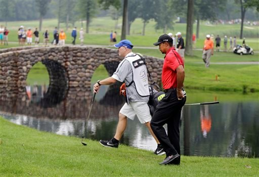 Tiger Woods and caddie Joe Lacava walk to the third green during the final round of the Bridgestone Invitational golf tournament Sunday, Aug. 3, 2014, at Firestone Country Club in Akron, Ohio. (AP Photo/Mark Duncan)