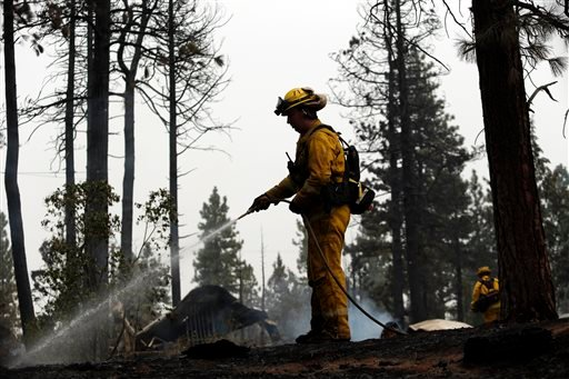 Matt Rietenbach, of the Shasta County Fire Dept. Montgomery Creek, hoses down hot spots left behind by the Eiler Fire on Monday, Aug. 4, 2014, in Hat Creek, Calif.