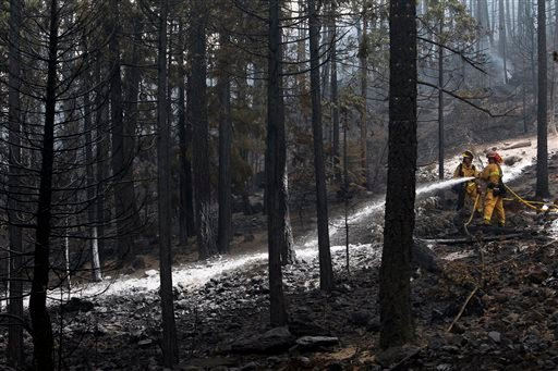 Firefighters try to stop the spreading of the Eiler Fire from moving closer to Burney, Calif, near Highway 89 on Tuesday, Aug. 5, 2014. (AP Photo/The Record Searchlight, Andreas Fuhrmann)