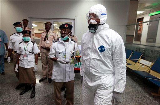 Nigerian health officials wait to screen passengers at the arrival hall of Murtala Muhammed International Airport in Lagos, Nigeria, Monday, Aug. 4, 2014. (AP Photo/Sunday Alamba)