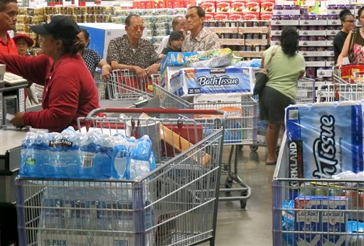 Shoppers stock up on cases of bottled water and other supplies in preparation for a hurricane and tropical storm heading toward Hawaii at the Iwilei Costco in Honolulu Aug. 5, 2014. (AP Photo/Audrey McAvoy)