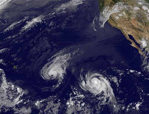This image provided by NOAA taken Wednesday Aug. 6, 2014 shows Hurricane Iselle, center, and tropical storm Julio, right. (AP Photo/NOAA)
