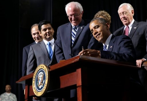President Barack Obama signs H.R. 3230, the Veterans' Access to Care through Choice, Accountability, and Transparency Act of 2014, Thursday, Aug. 7, 2014, at the Wallace Theater in Fort Belvoir, Va. (AP)