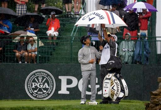 Ryo Ishikawa, of Japan, puts up an umbrella on the range before the second round of the PGA Championship golf tournament at Valhalla Golf Club on Friday, Aug. 8, 2014, in Louisville, Ky. (AP Photo/David J. Phillip)