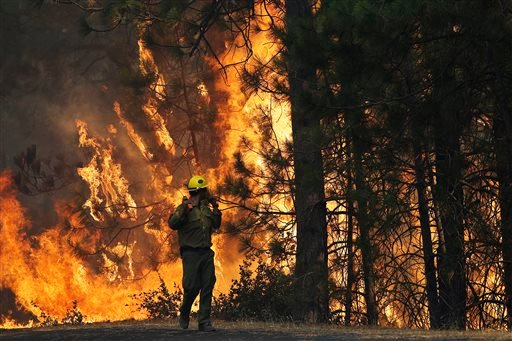 In this Aug. 25, 2013 file photo, firefighter A.J. Tevis watches the flames of the Rim Fire near Yosemite National Park, Calif.