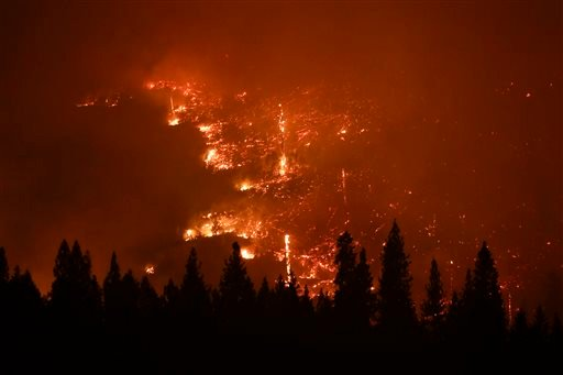 In this Aug. 24, 2013 file photo, a forest smolders as the Rim Fire continues to burn near Yosemite National Park, Calif.