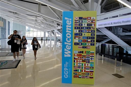 Three people walk past a welcome sign for the 9th International Gay Games inside the downtown convention center in Cleveland Thursday, Aug. 7, 2014.