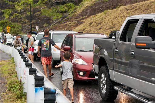 Onlookers park on the side of the road to look at the waves at Makapuu Beach, Friday, Aug. 8, 2014, in Waimanalo, Hawaii. Tropical Storm Iselle knocked out power, caused flooding and downed trees when it crossed onto the Big Island. (AP Photo/Marco Garcia
