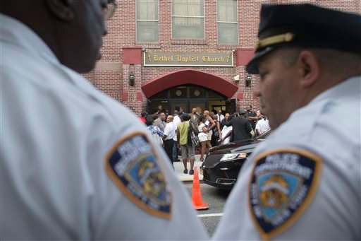 In this July 23, 2014 file photo, a pair of New York City police officers stand at their post as mourners arrive for the funeral service of Eric Garner at Bethel Baptist Church in the Brooklyn borough of New York.