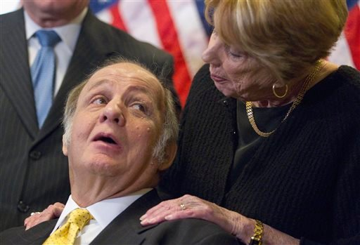 This March 30, 2011, file photo shows former White House press secretary James Brady, left, who was left paralyzed in the Reagan assassination attempt, looking at his wife Sarah Brady, during a news conference on Capitol Hill in Washington..