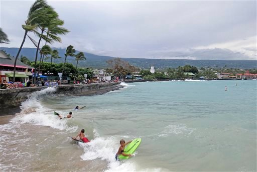Young board surfers ride storm-driven waves under the seawall on Ali'i Drive in Kailua-Kona, Hawaii, Friday, Aug. 8, 2014.