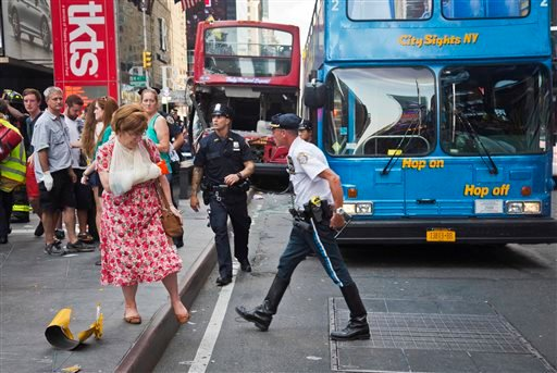 In this Aug. 5, 2014 file photo, woman, her arm bandaged and in a sling, leaves after being treated at the scene of a traffic accident apparently involving two double-decker tour buses in New York's Times Square.