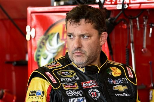 In this Friday, Aug. 8, 2014 photograph, Tony Stewart stands in the garage area after a practice session for Sunday's NASCAR Sprint Cup Series auto race at Watkins Glen International, in Watkins Glen N.Y.