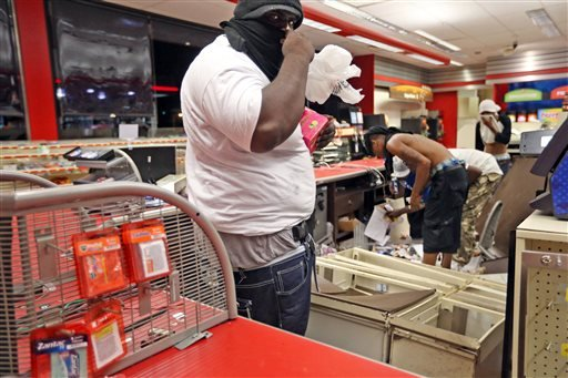 People are seen in a store Sunday, Aug. 10, 2014, in Ferguson, Mo.