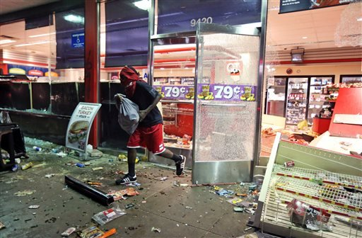 A man leaves a store on Sunday, Aug. 10, 2014, in Ferguson, Mo.