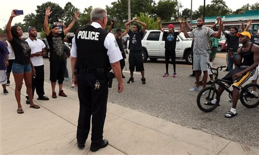 Protestors blocking Florissant Road raise their hands after being approached by police officers who asked them to stop blocking the street in front of the Ferguson police department on Sunday, Aug. 10, 2014.
