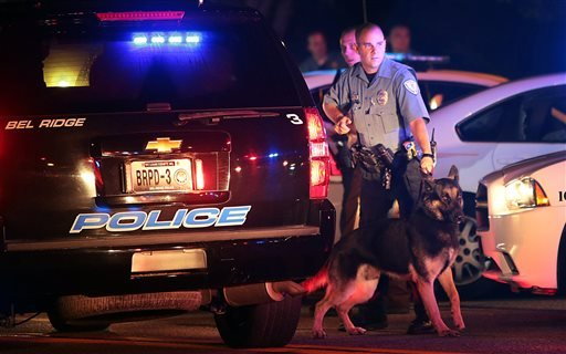 Police officers patrol the area Sunday, Aug. 10, 2014, in Ferguson, Mo.
