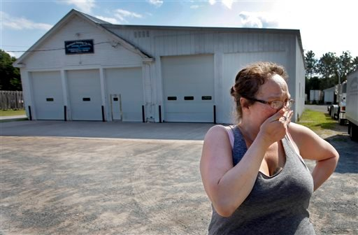 Lynn Hardy cries Sunday Aug. 10, 2014, in front of the Westward Painting Co. Inc in Lyons Falls, N.Y., where race car driver Kevin Ward Jr. kept and worked on his car and worked with his father Kevin Sr. in the painting business.