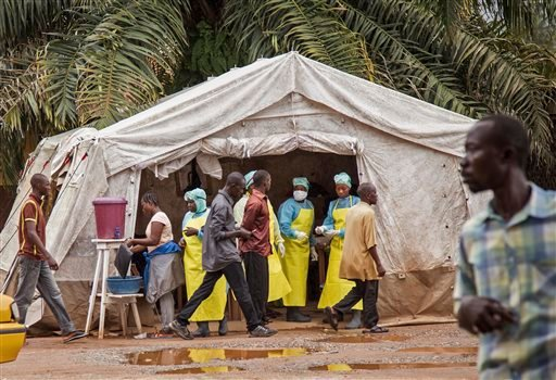 In this photo taken Saturday, Aug. 9, 2014, health workers, center rear, screen people for the deadly Ebola virus before entering the Kenema Government Hospital in Kenema, 300 kilometers, (186 miles) from the capital city of Freetown, Sierra Leone.