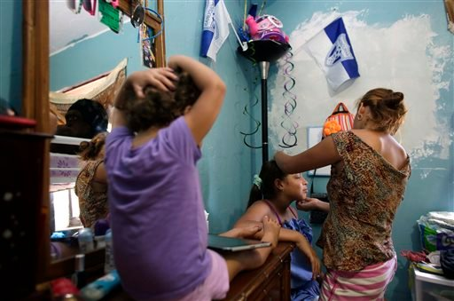 In this July 24, 2014 photo, Nicole Valerio Zelaya, center, 12, has her eyebrows done by her sister Anita Medina Zelaya, right, 16, at their mother's home in Miami.