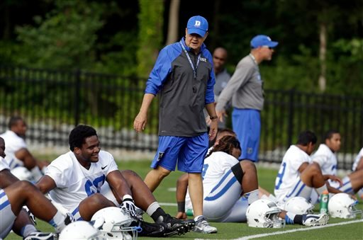 In this Monday, Aug. 5, 2013, file photo, Duke coach David Cutcliffe chats with players as they stretch during an NCAA college football practice in Durham, N.C.