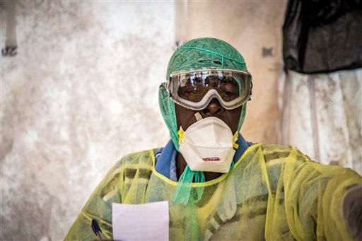 In this photo taken Monday, Aug. 11, 2014, a health worker examines patients for Ebola inside a screening tent, at the Kenema Government Hospital situated in the Eastern Province around 300 km, from the capital city of Freetown in Kenema, Sierra Leone.