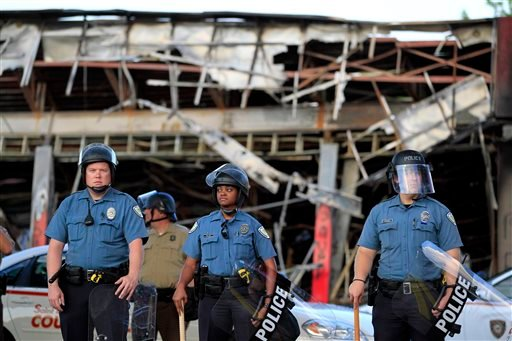 Police wearing riot gear stage outside the remains of a burned convenience store Monday, Aug. 11, 2014, in Ferguson, Mo.