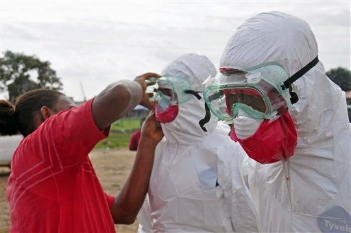 A health worker assists a colleague with his protective gear, as they collect the body of a man suspected to have died from the ebola virus, in Monrovia, Liberia, Tuesday, Aug. 12, 2014. (AP)