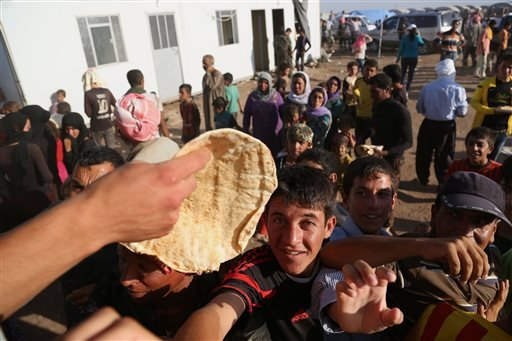 Displaced Iraqis from the Yazidi community gather for food at the Nowruz camp, in Derike, Syria, Tuesday, Aug. 12, 2014. (AP)
