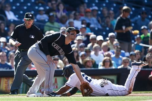 Padres' Yangervis Solarte is safe at third as Rockies third baseman Nolan Arenado applies a late tag in the first inning of a baseball game Aug. 13, 2014, in San Diego. (AP Photo/Lenny Ignelzi)