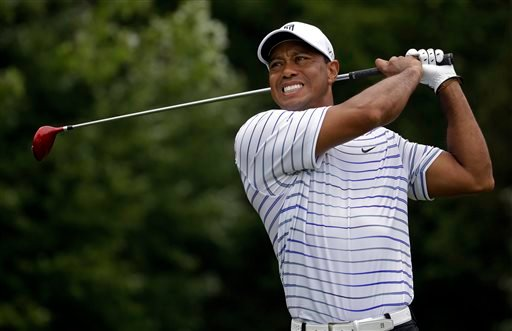 In this Friday, Aug. 8, 2014 file photo, Tiger Woods winces after tee shot on the sixth hole during the second round of the PGA Championship golf tournament at Valhalla Golf Club in Louisville, Ky.