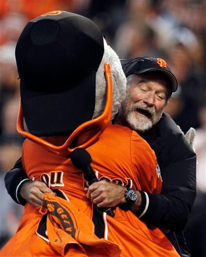 In this file photo from Thursday, Oct. 7, 2010, actor Robin Williams hugs San Francisco Giants mascot Lou Seal during the first inning of Game 1 of baseball's National League Division Series in San Francisco.