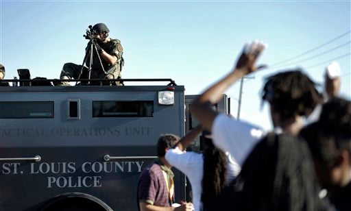 A member of the St. Louis County Police Department points his weapon in the direction of a group of protesters in Ferguson, Mo. on Wednesday, Aug. 13, 2014. (AP Photo/Jeff Roberson)