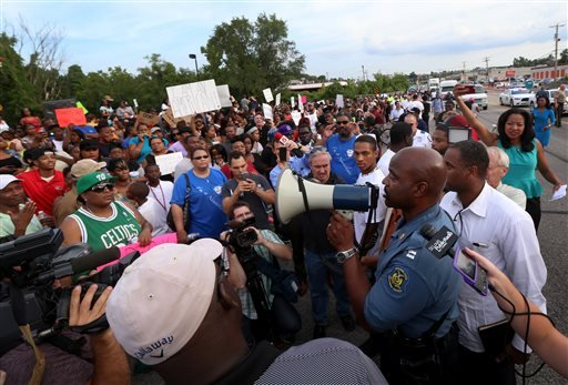 Missouri State Highway Patrol Capt. Ronald Johnson addresses the crowd of protesters, asking them to stay on the sidewalk and not block traffic Thursday, Aug. 14, 2014, in Ferguson, Mo.