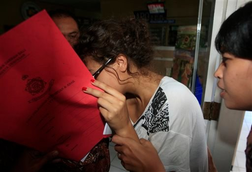 Heather Mack, covering her face, is led to a hospital for a medical check by Indonesian police officers in relation to the death of her mother Sheila von Wiese-Mack in Bali, Indonesia, Friday, Aug. 15, 2014.