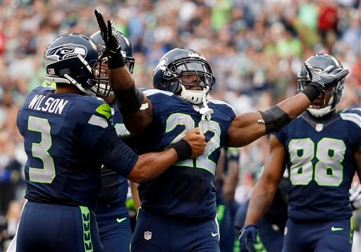 Seattle Seahawks strong safety Jeron Johnson (23) celebrates a tackle with outside linebacker K.J. Wright, left, in the first half of a preseason NFL football game against the San Diego Chargers, Friday, Aug. 15, 2014, in Seattle.