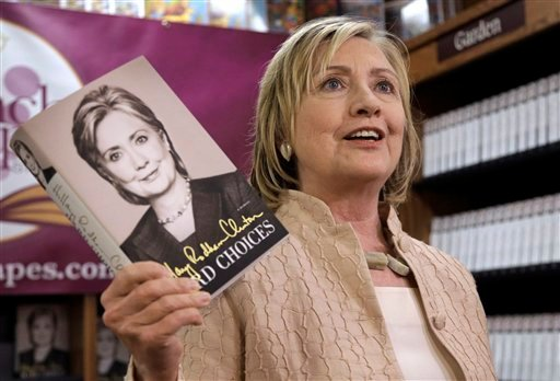 """In this Aug. 13, 2014, photo, former Secretary of State Hillary Rodham Clinton holds her memoir """"Hard Choices"""" at Bunch of Grapes Bookstore, in Vineyard Haven, Mass., on the island of Martha's Vineyard, during a book signing event for her memoir."""