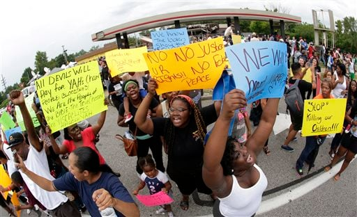 Protesters chant Friday, Aug. 15, 2014, outside a convenience store that was looted and burned following the shooting death of Michael Brown by police nearly a week ago in Ferguson, Mo.