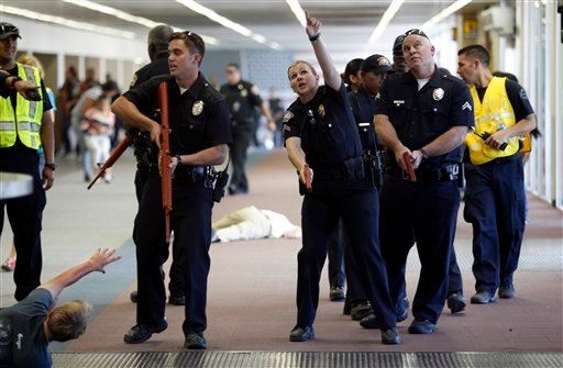 In this Oct. 6, 2013 photo, Los Angeles Airport Police team up with City of Los Angeles Police officers in a joint training session on counterterrorism, searching for armed men playing out several shooting scenarios with youth and adult volunteers acting.